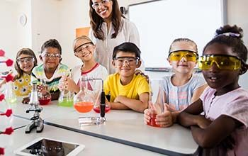 Students wearing safety goggles smiling at the table holding their beakers with multi colored liquid inside them.