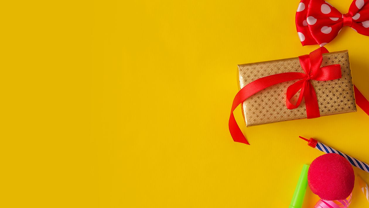 a wrapped present with a red ribbon, a red bow tie, streams and pink ribbon on a yellow background